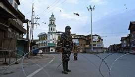 Security personnel stand guard on a street during a lockdown in Srinagar
