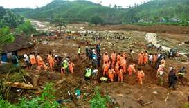 Volunteers, local residents and members of National Disaster Response Force (NDRF) search for surviv