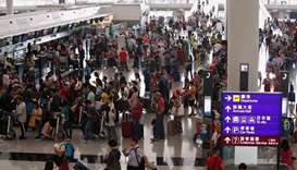 Passengers queue as the airport reopened a day after flights were halted due to a protest, at Hong K