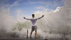 A man reacts as waves crash against the seafront on Enoshima Island on the coast of Kanagawa prefect
