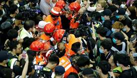 Medics attempt to remove an injured man who anti-government protesters said was an undercover police