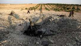 Rebel fighters gather near the remains of a downed warplane near the town of Khan Sheikhun in the so