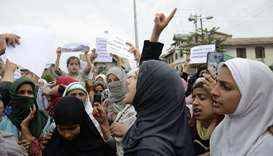 Protesters shout slogans at a rally against the Indian government's move to strip Jammu and Kashmir