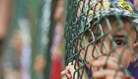 A Kashmiri child looks from behind a fence at a protest site after Friday prayers yesterday.