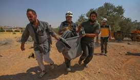 Members of the Syrian Civil Defense (White Helmets) carry away in a blanket a person rescued from th