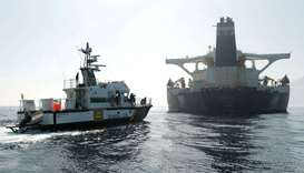 A Spanish Civil Guard ship sails next to Iranian oil tanker Grace 1, with its name and Panama's flag