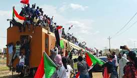 Sudanese civilians ride on the train to join in the celebrations of the signing of the Sudan's power