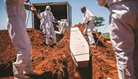 Municipal Johannesburg Morgue workers bury a coffin at the Olifantsvlei Cemetery in Johannesburg.