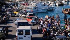 Twenty-seven unaccompanied minors leave the harbour in Lampedusa in police vans
