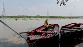 An Indian man sits on a boat on the banks of the Yamuna river as water level has risen due to heavy