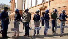 Riot police officers keep watch outside the Tredgold Building Magistrate court in Bulawayo, Zimbabwe