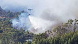 A helicopter carries water to fight a forest fire seen in the village of Guia on the Canary Island o