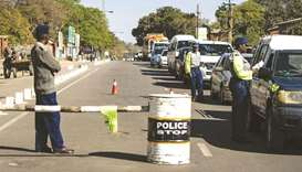 Police officers conduct searches on vehicles along a major road leading into Bulawayo yesterday.