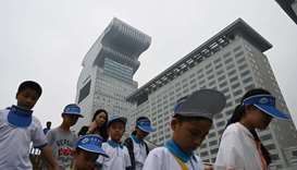 Children walk past Pangu Plaza, a skyscraper which dominates the area next to the Bird's Nest Olympi