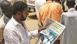 A Sudanese man reads the newspaper yesterday headlining the court appearance of Sudan's deposed mili