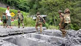 Myanmar army soldiers walk on a bridge on the Myanmar-China major trading route destroyed in an insu
