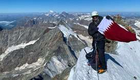 Qatari adventurer Fahad Badar poses with the national flag