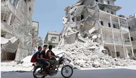 A Syrian man drives a motorcycle past destroyed buildings in the town of Ariha, in the south of Syri
