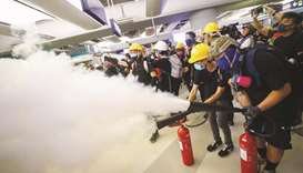 Protesters fire nitrogen extinguishers toward riot police during a standoff at Yuen Long MTR station