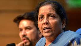 Union Finance Minister Nirmala Sitharaman (R) speaks as she attends a press conference along with Me