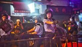 Police officers point their guns at protesters in Tseun Wan in Hong Kong