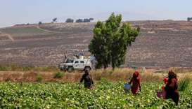 Farmers work in the plain of Marjayoun on the outskirts of the southern Lebanese village of Khiam, o