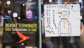 Protesters stick posters outside a shopping mall in a rally to support Cathay Pacific staff in Hong