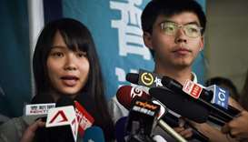 Pro-democracy activists Agnes Chow (L) and Joshua Wong (R) speak to the press after they were releas