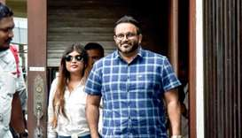 Jailed former vice-president Ahmed Adeeb (R) walks along with his wife Mariyam Nashwa (L) as he retu
