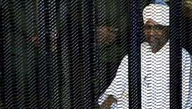 Sudan's former president Omar Hassan al-Bashir sits guarded inside a cage at the courthouse where he
