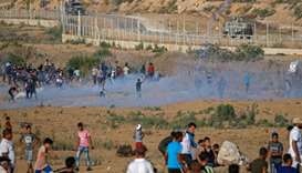 Palestinian protesters flee from tear gas fired by Israeli forces across the fence during clashes al