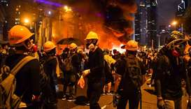 Protesters stand before a barricade they set on fire in the Wan Chai district in Hong Kong