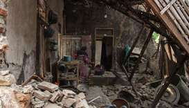 A villager looks for her belongings at her damage house in Pandeglang, Banten province, after a stro