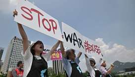 "Anti-war activists hold placards reading ""Stop War Exercises,"" during a rally against planned South"