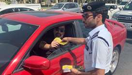 An official of Traffic Patrol and Investigation Department distributing an awareness booklet at Doha