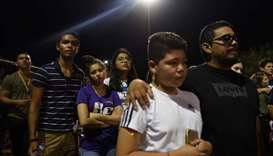 People gather for a vigil a day after a mass shooting at a Walmart store in El Paso, Texas