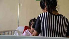 A mother takes care of her daughter suffering from Dengue at the San Lazaro Hospital.