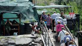 Russia-backed separatists watch as people walk across a destroyed bridge between the Ukraine-control