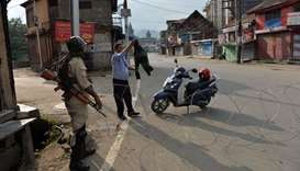 A security guard of a bank shows his sweater to a solider at a roadblock in Srinagar