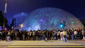 People watch the dots of laser pointers move across the facade of the Hong Kong Space Museum during