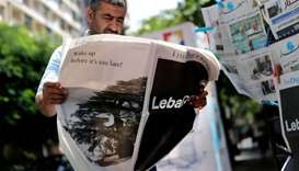 "A man checks a copy of the Lebanese local English-language newspaper ""The Daily Star"" in the capital"