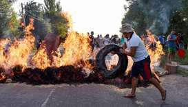 A protester puts a tyre on a burning barricade during clashes between supporters of Kyrgyzstan's for
