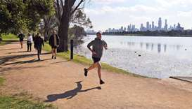 A jogger runs beside Albert Park Lake in Melbourne