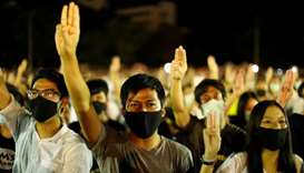 Pro-democracy protesters do a three-fingered salute as they attend a rally to demand the government
