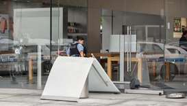 A Chicago Police officer inspects an Apple store that was vandalized in Chicago, Illinois, US