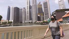 A woman walks across a bridge overlooking the financial business district in Singapore yesterday. Si
