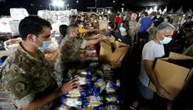 Lebanese army members and volunteers prepare aid to be distributed to people in the aftermath of a m