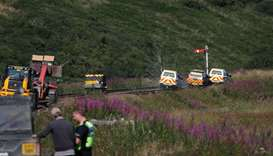 Emergency service vehicles ride along the tracks near the scene of a derailed passenger train, near