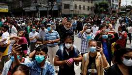 People wearing face masks gather as they observe the chariot festival amid the outbreak of the coron