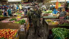 An armed police officer patrols at a public market where wearing face masks and face shields is mand
